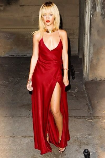 Red maxi dress made of silk slit with deep V-neckline and gold choker necklace