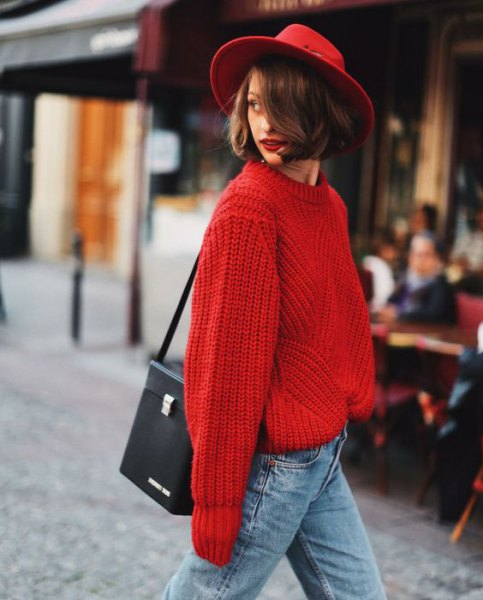 red felt hat with a chunky red sweater with light blue jeans
