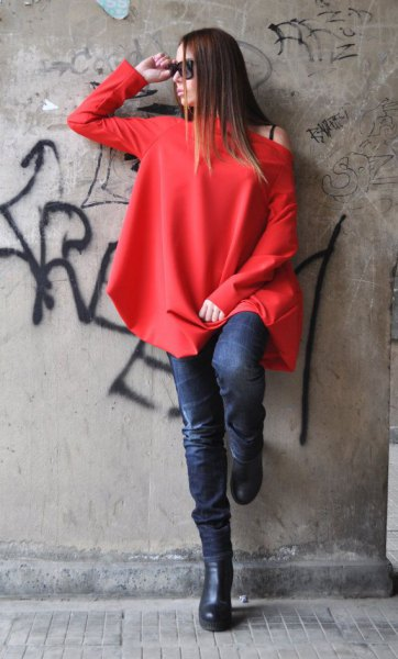 red long-sleeved top with one shoulder and dark blue skinny jeans