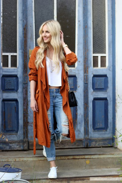 red longline trench coat with torn boyfriend jeans and white sneakers