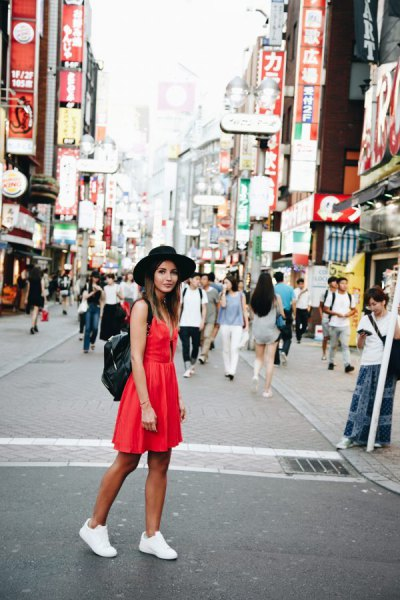 red mini summer dress with white sneakers and black felt hat