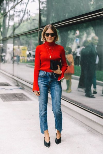 red bell-sleeved sweater with blue neckline and blue-cut jeans with straight legs
