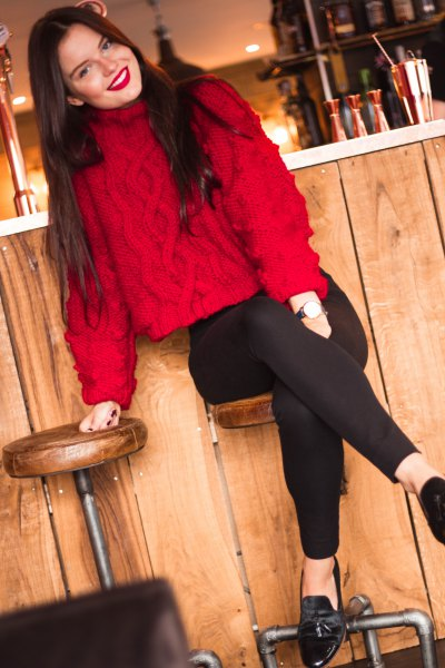 red knitted sweater with stand-up collar and black slim fit jeans