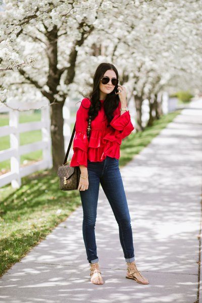 Skinny jeans with a red ruffled blouse and cuff