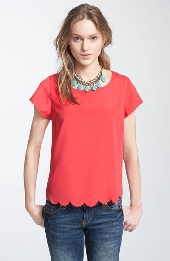 red scalloped short-sleeved shirt with blue skinny jeans