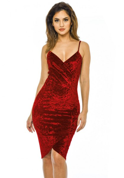 Red, figure-hugging velvet dress with a deep V-neckline and spaghetti strap
