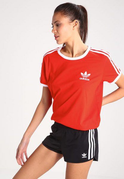 red t-shirt with black mini sports shorts