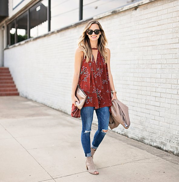 Red sleeveless tunic with a V-neckline and blue ribbed skinny jeans