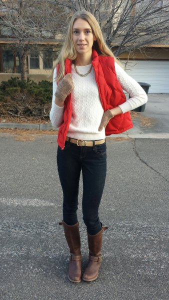 red waistcoat with white knitted sweater with round neckline and black skinny jeans