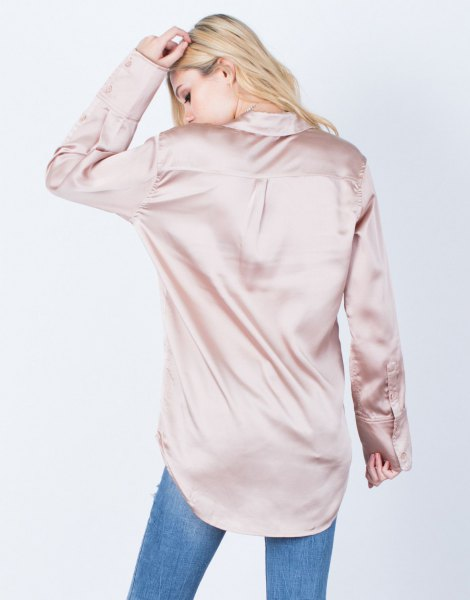 Rose gold oversized silk shirt with buttons and blue jeans