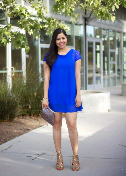 Royal blue mini sheath dress made of lace with cap sleeves and metallic strappy heels