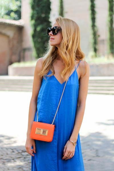 Royal blue mini sheath dress with V-neck and orange mini handbag