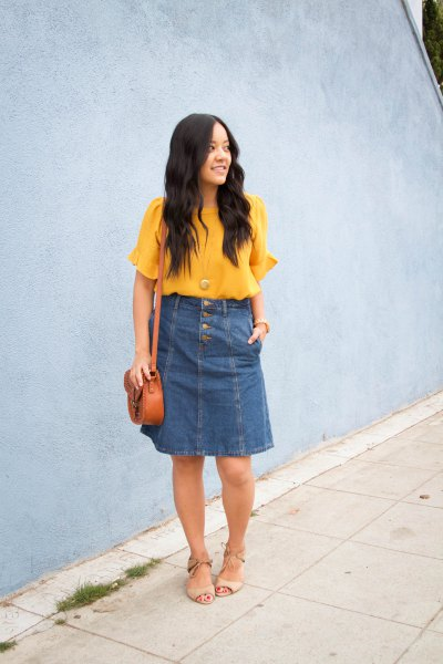 yellow chiffon blouse with short sleeves and blue knee-length denim skirt