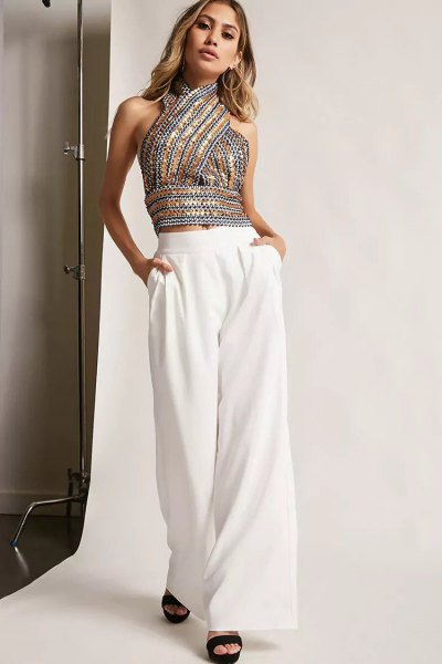 Sequin halter top with silver and gold pattern and white trousers with wide legs