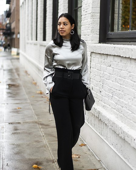 silver metallic blouse with black trousers with a high waist and wide legs