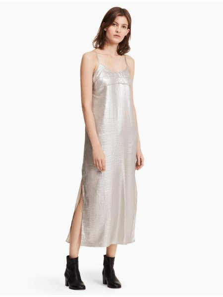 silver maxi dress with spaghetti strap and scoop neckline and black leather ankle boots