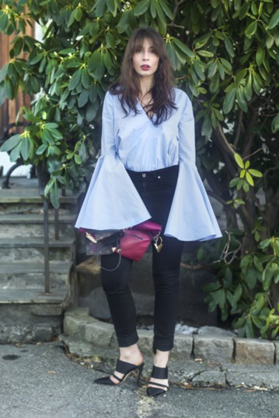 sky blue, exaggerated bell-sleeved blouse with black skinny jeans