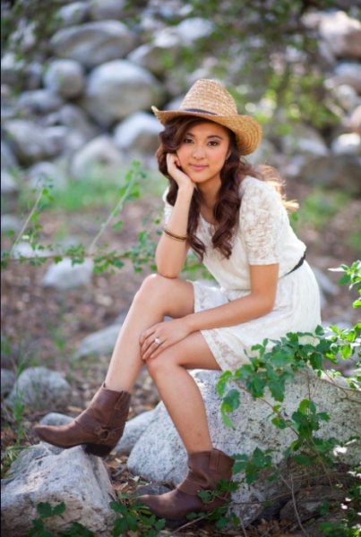 Straw cowboy hat with a white mini lace dress with short sleeves and a belt