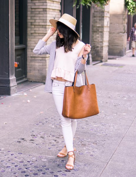 Straw hat with a cashmere cardigan draped over the shoulder and a crop top