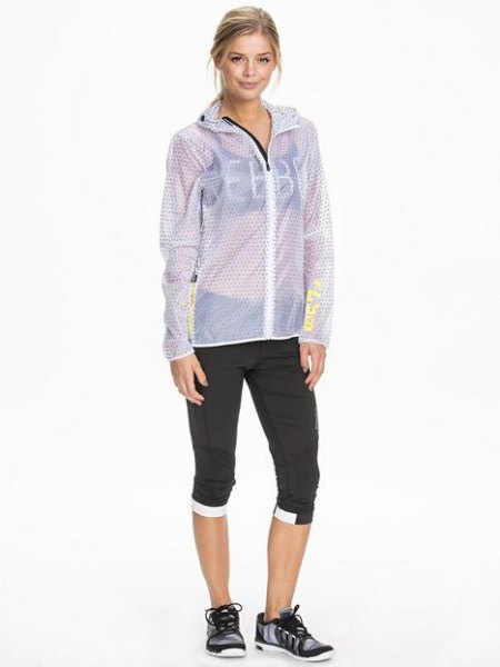 blue-green, semi-transparent jacket with black sports bra and cropped jogger pants