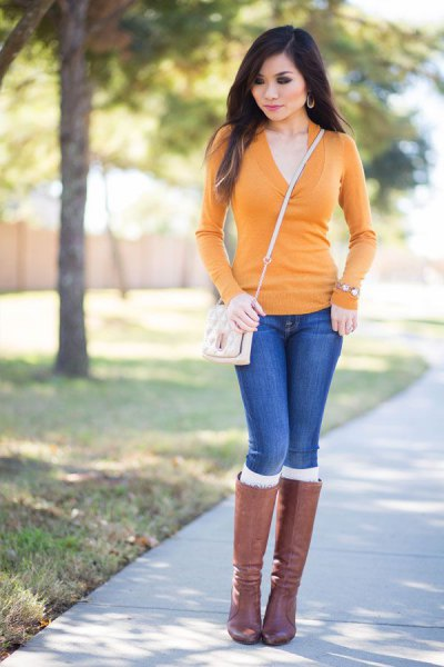 Custom-fit sweater with mustard and V-neckline, blue jeans and gray knee-high boots