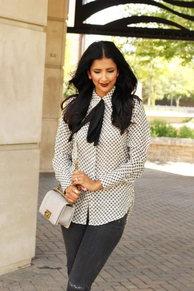 white and black patterned tie blouse gray jeans