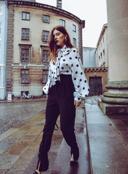 white and black polka dot blouse with a polka dot tie on the front and high pants