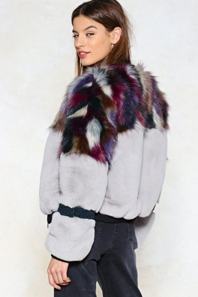 white and black printed faux fur jacket with dark blue trousers