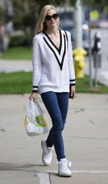 white and black ribbed sweater with V-neckline and dark blue skinny jeans