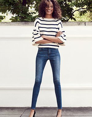 white and black striped wide-sleeved sweater and blue skinny jeans