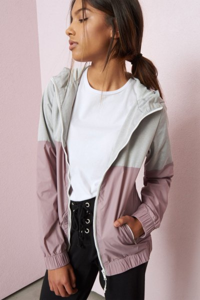 white and light gray color block Nike windbreaker with black lace-up jeans