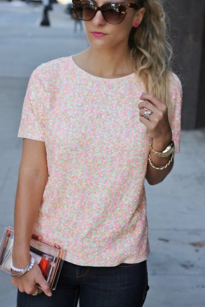 Short-sleeved blouse with a white and peach-colored pattern and black skinny jeans