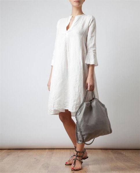 Knee-length dress made of white linen with bell sleeves and sandals