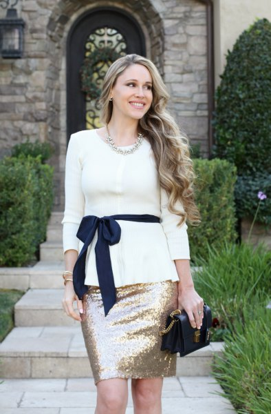 white peplum sweater with belt and rose gold-colored mini skirt made of sequins