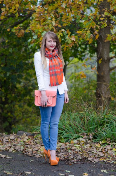 white blazer with blue skinny jeans and an orange checked scarf