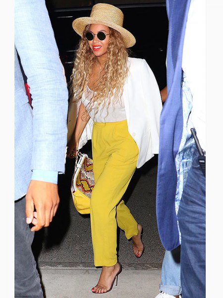 white blazer with mustard-yellow trousers with straight legs and straw hat