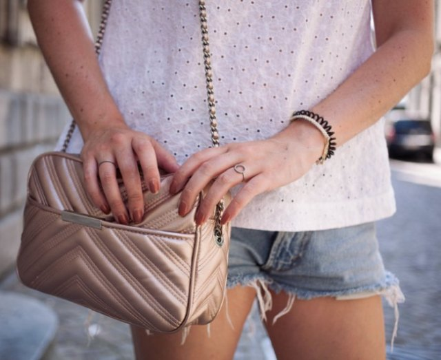 white blouse with blue denim shorts and rose gold wallet