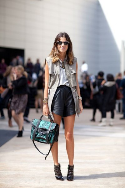 white blouse with long vest and flowing shorts made of black leather