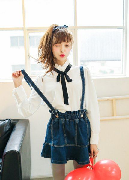 white shirt with buttons, black bow tie and dark blue pleated skirt