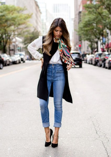 white shirt with buttons, black long vest and blue jeans with high waist