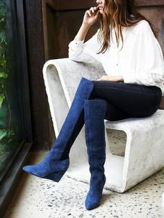 white shirt with buttons and blue suede boots above the knee