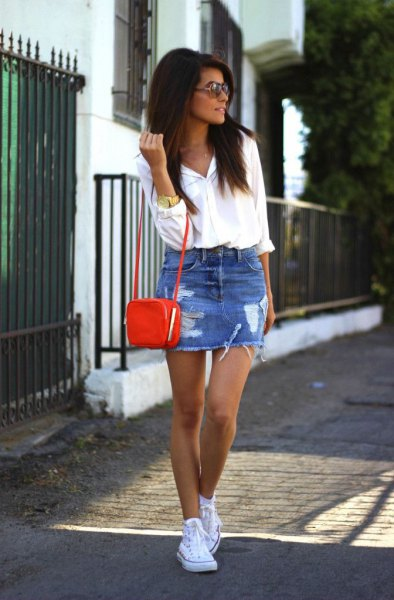 white shirt with buttons, a blue torn minirim skirt and a small brown shoulder bag
