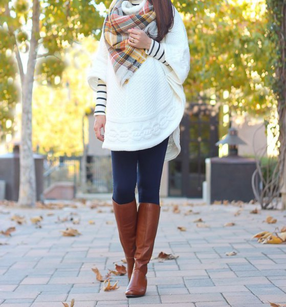 white cable knit cape with checked scarf and knee-high boots made of brown leather
