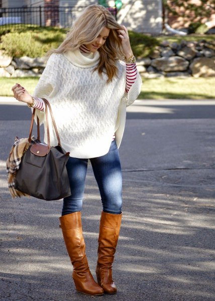 white cable knit poncho sweater with blue skinny jeans and knee-high boots made of brown leather