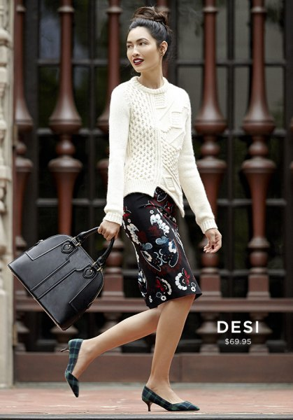 white cable knit sweater and black knee-length floral skirt