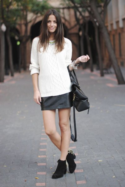 white cable knit sweater with black leather skirt and mini boots with heels