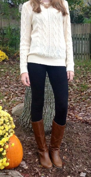 white cable knit sweater with black leggings and knee-high boots made of brown leather