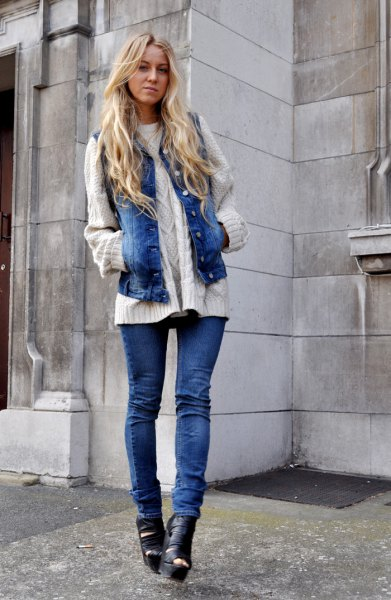 white cable knit sweater with blue denim motorcycle vest and boots