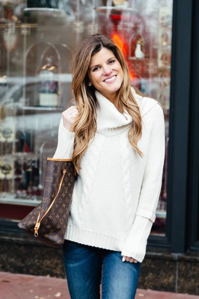 white cable knit sweater with blue slim fit jeans