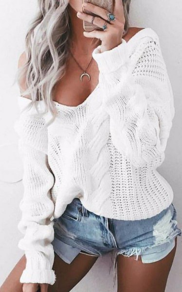 white cable knit sweater with wide V-neckline and blue mini denim shorts